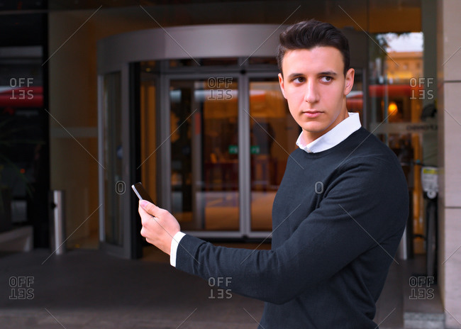 Young traveler looks at his mobile in front of the hotel