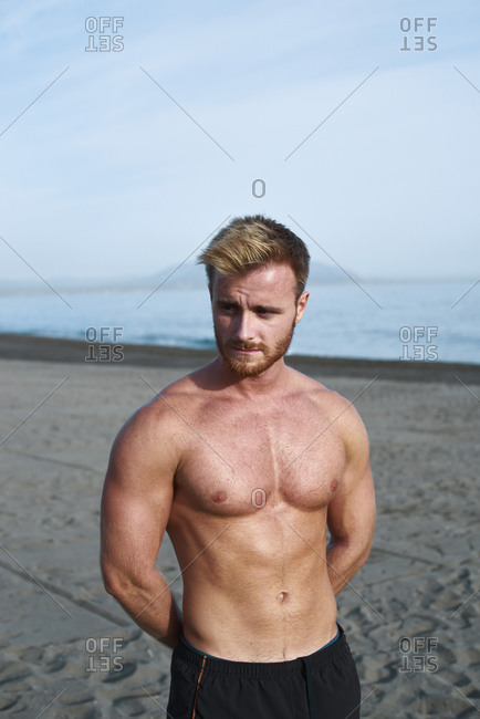 Young shirtless redhead athlete on the beach