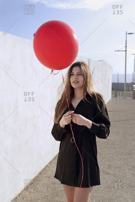 Young woman carries a red gas balloon in front of a white wall