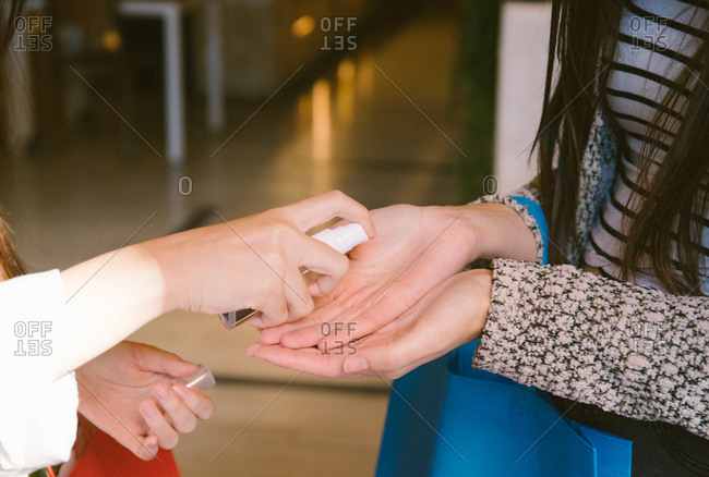 Crop of a girl's hands giving hydroalcoholic gel to another girl at the entrance of a restaurant
