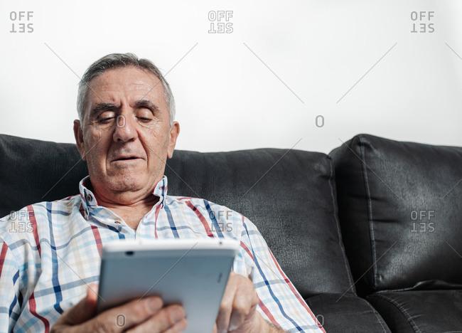 Senior man using tablet on sofa
