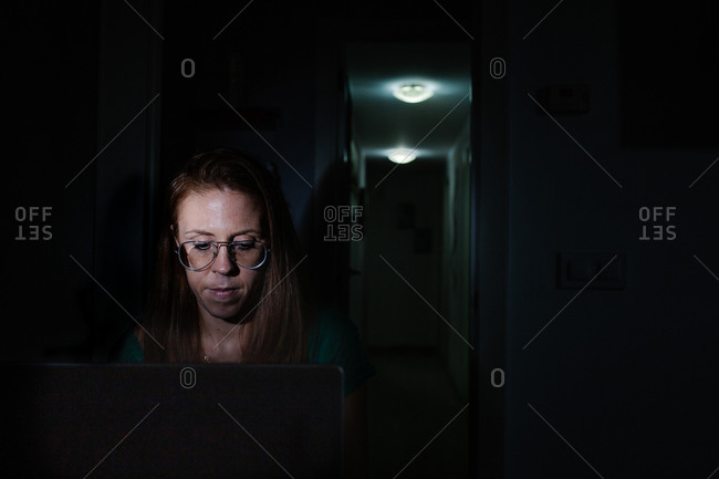 Woman working with laptop at night