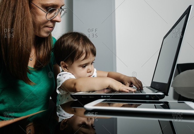 Busy woman with little child working on laptop
