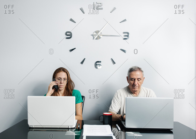 Mature couple teleworking in home office