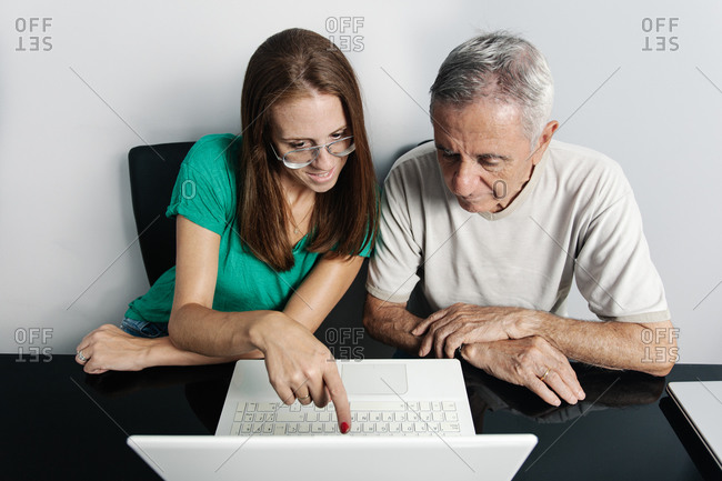 Woman helping father with laptop