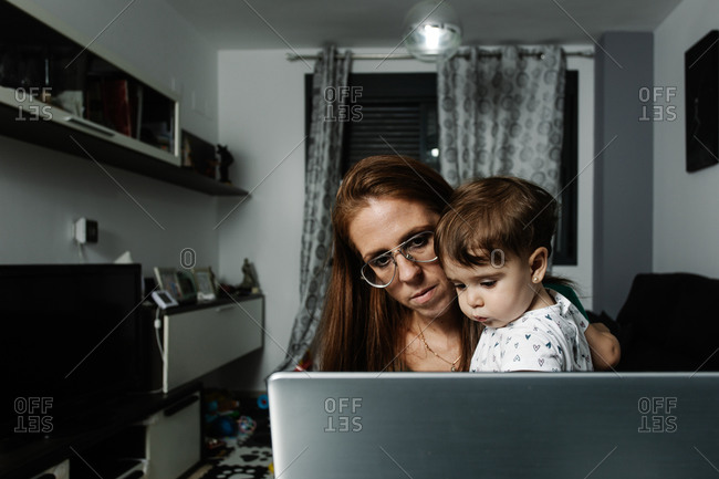 Woman with little kid on arms using laptop at home