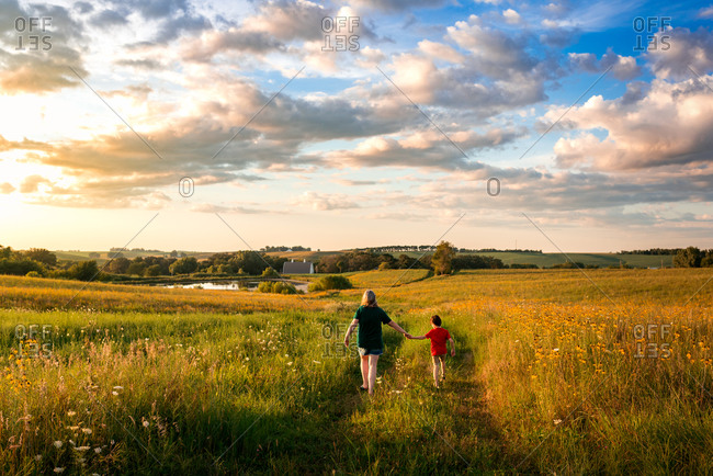 Mother and son walking through a field of flowers on a rural farm