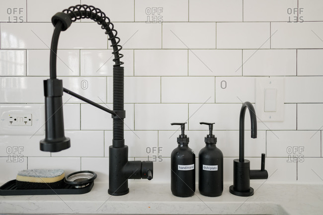 Kitchen sink with black fixtures and soap