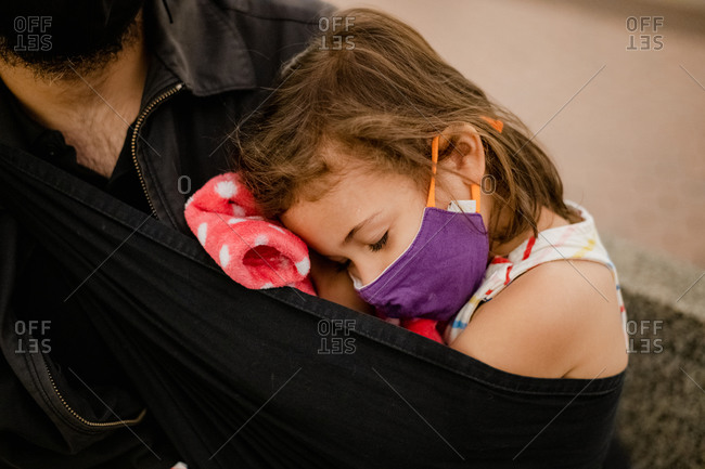 Little girl sleeping with face mask on her dad