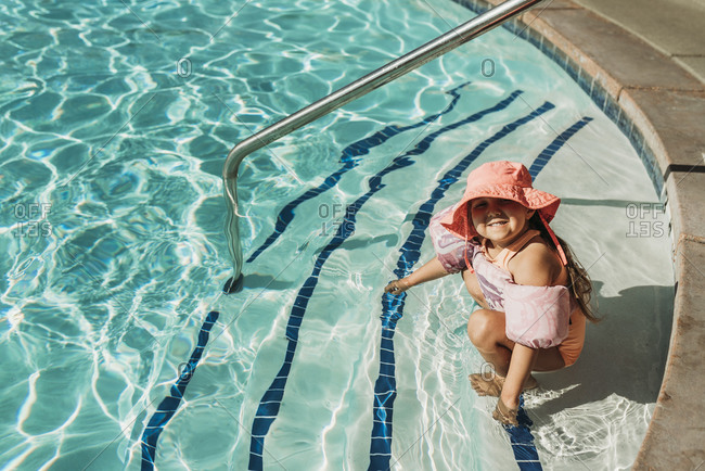Young preschool age girl swimming in pool on vacation in Palm Springs