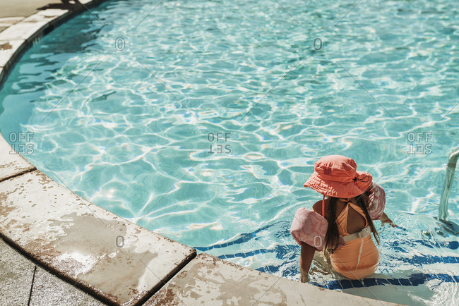 Behind view of little girl swimming in pool on vacation Palm Springs