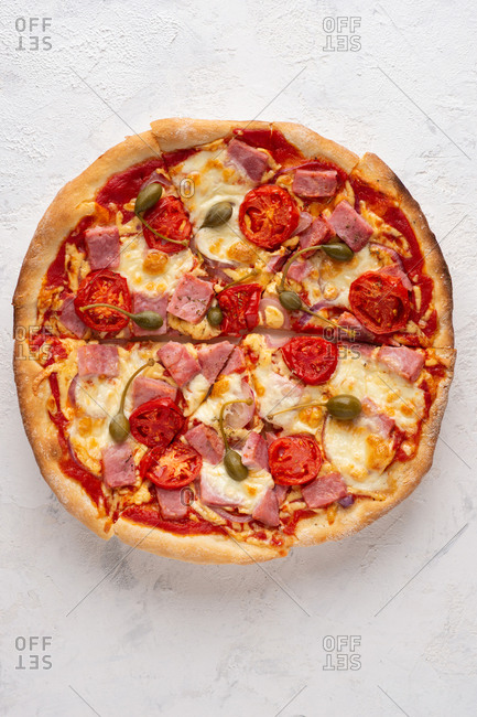 Overhead view of fresh sliced pizza with cheese, ham, tomatoes and capers