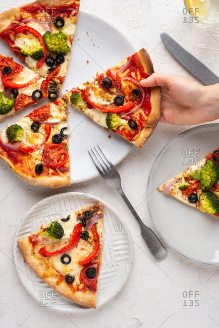Overhead view of fresh sliced pizza with mozzarella cheese, broccoli, tomatoes, red onion, olives and paprika. Human hand holding slice of pizza