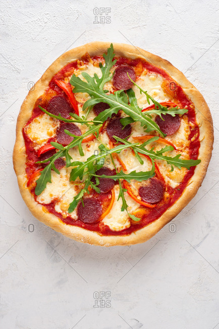 Overhead view of fresh whole pizza with sausage, mozzarella cheese, arugula and paprika