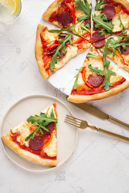 Overhead view of fresh sliced pizza with sausage, mozzarella cheese, arugula and paprika