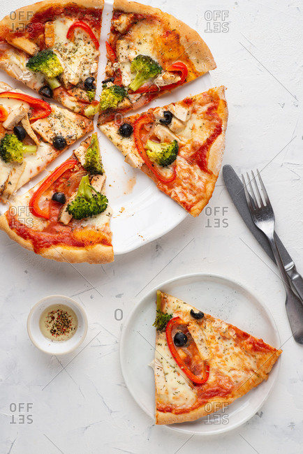 Overhead view of fresh sliced pizza with white chicken meat, olives and broccoli served on white ceramic plate