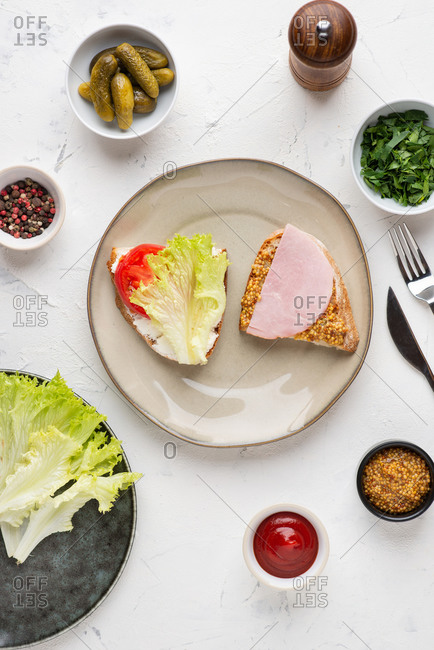 Overhead view of the plate with meat and vegetables open sandwiches served with pickles and mustard