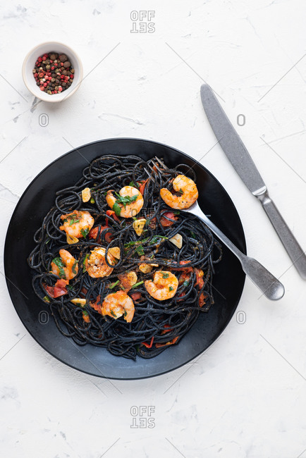 Black squid ink pasta with red tomato sauce and shrimps served on black plate