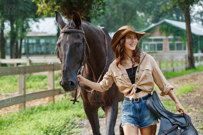 Outdoor happy young woman the horse