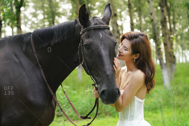 A beautiful young woman intimacy stroked the horse