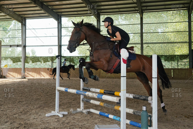 Riding a horse jump barrier bar young woman