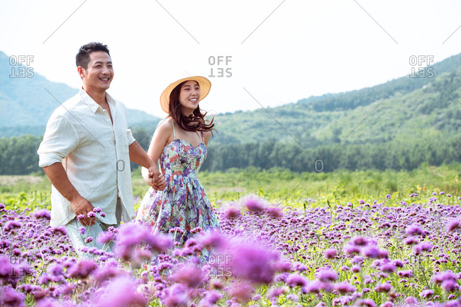 Young couple walking hand in hand in the sea