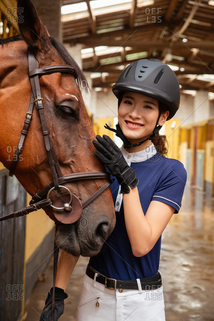 Happy young woman and a horse in the barn