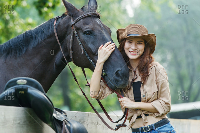 Happy young woman of outdoor arm around the horse