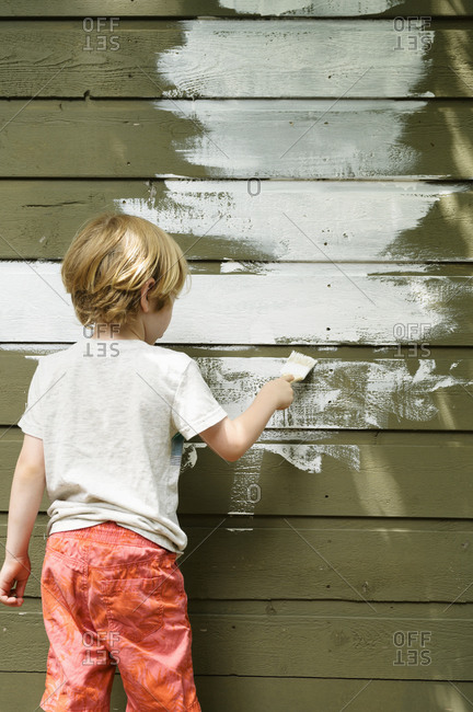 Boy (4-5) painting cottage wall