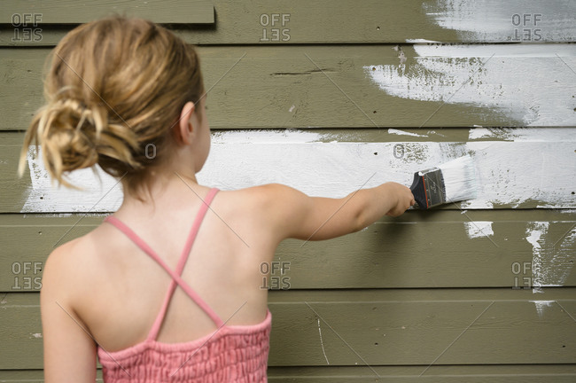 Girl (6-7) painting cottage wall