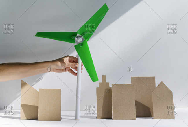Woman's hand holding scale model of wind turbine