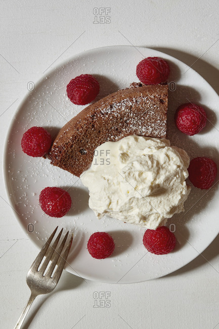 Chocolate cake with whipped cream and raspberries on plate