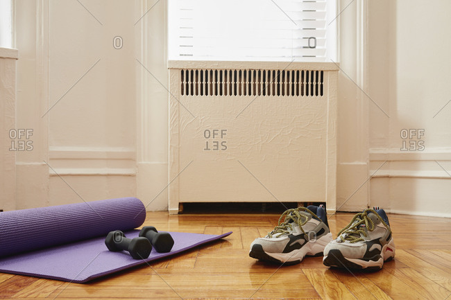 Yoga mat, weights and sports shoes on floor at home gym