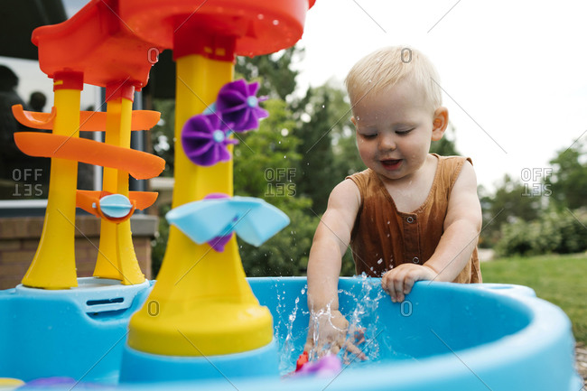 Baby boy(18-23 months) playing with water toys in garden