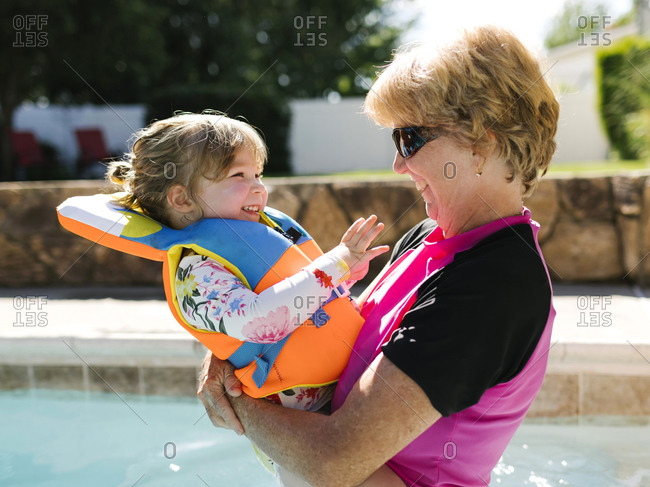 Grandmother holding toddler girl (2-3) on outdoor swimming pool