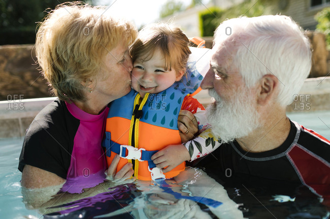 Grandparents with toddler girl (2-3) standing in outdoor swimming pool