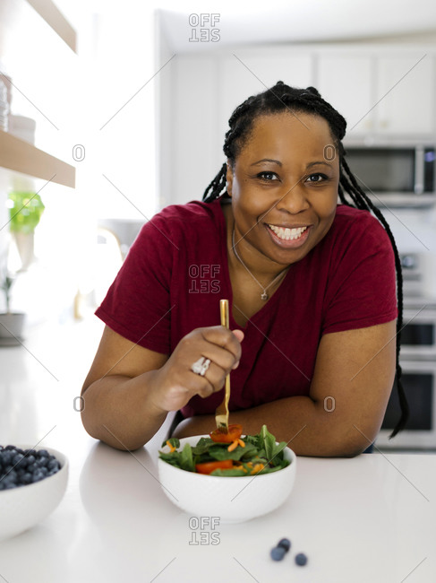Portrait of smiling woman having healthy salad in kitchen
