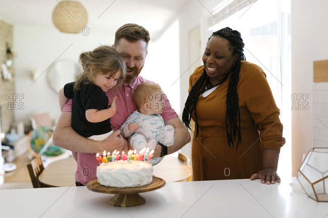 Woman and man with kids (2-3, 9-11 months) celebrating birthday at home