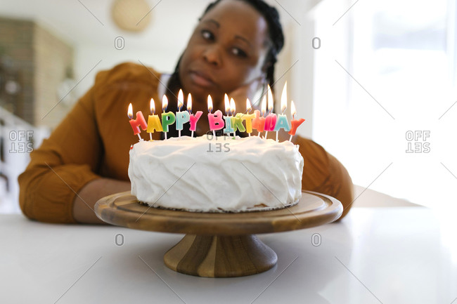 Portrait of woman behind birthday cake