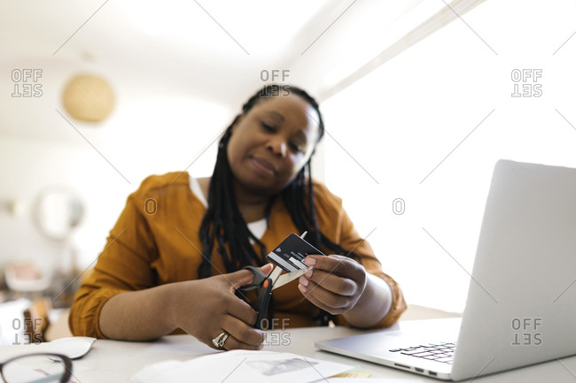Woman cutting credit card with scissors while working in home office