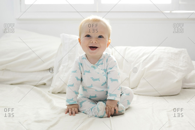 Smiling baby boy (6-11 months) sitting on bed