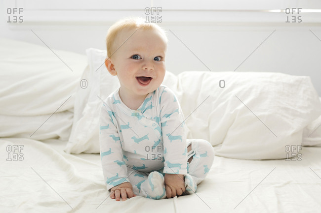 Baby boy (6-11 months) lying on bed