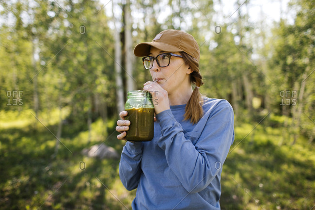 USA, Utah, Uinta National Park, Woman wearing eyeglasses and baseball cap drinking coffee from jar in forest