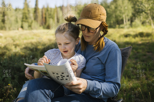USA, Utah, Uinta National Park, Mother and daughter (6-7) doing crossword in meadow in forest