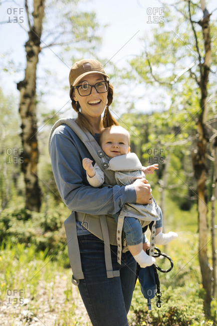 USA, Utah, Uinta National Park, Portrait of smiling woman with baby son (6-11 months) in baby carrier in forest
