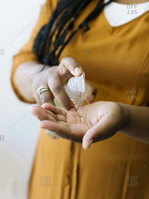 Close-up of woman cleaning hands with hand sanitizer
