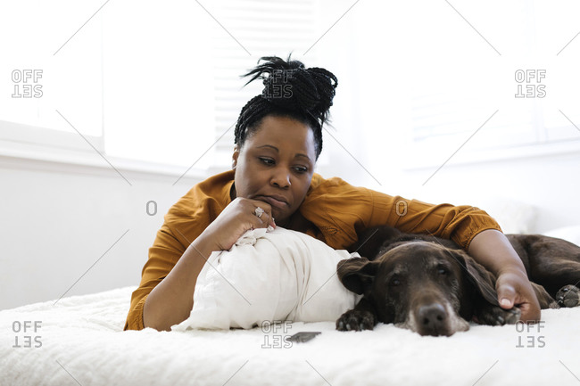 Sad woman lying on bed with dog