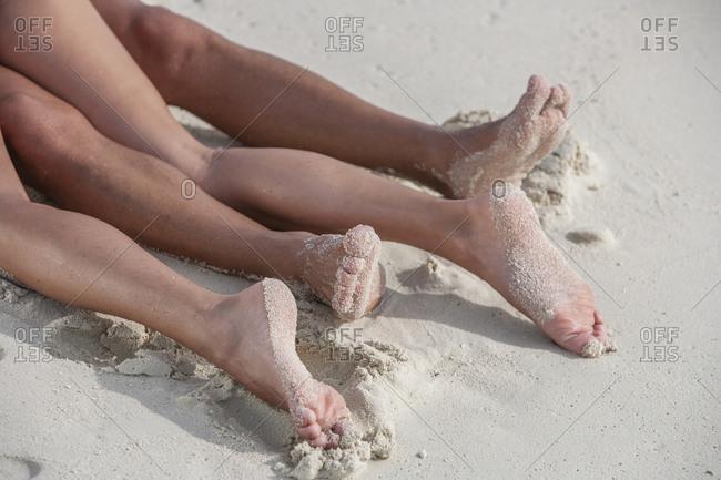 Legs of couple lying on beach
