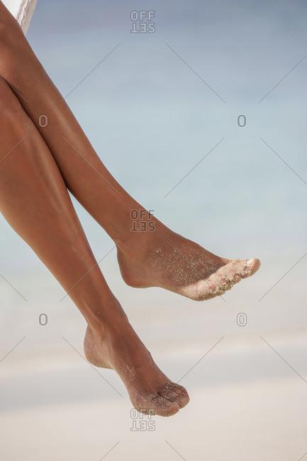 Woman's legs at tropical beach