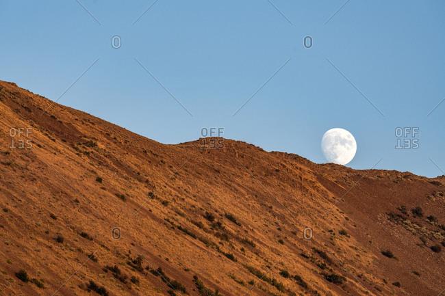 USA, Idaho, Sun Valley, Moon behind hill